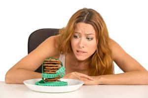 woman on diet looking at baked cookies with tape measure