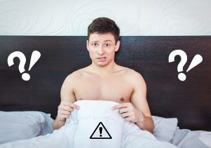man with erectile issue sitting on bed, low libido