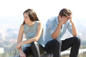 disappointed woman turning her back on defeated man, feeling not good enough