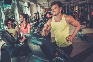 happy fit man running on treadmill in gym