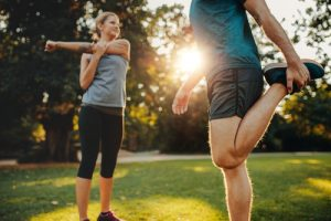 man and woman stretching in park before exercise