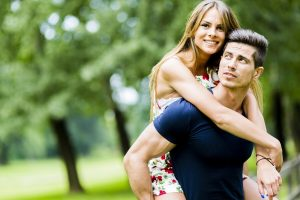man carrying smiling woman on his back
