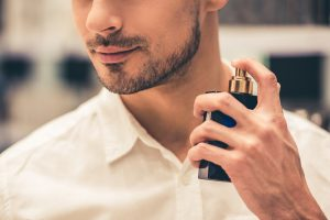 attractive man spraying perfume on neck
