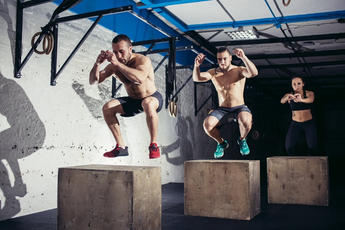 athletic men and woman doing box jump workout