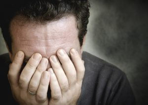 frustrated man covering face with hands