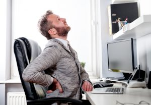 man having back pain after typing for long hours