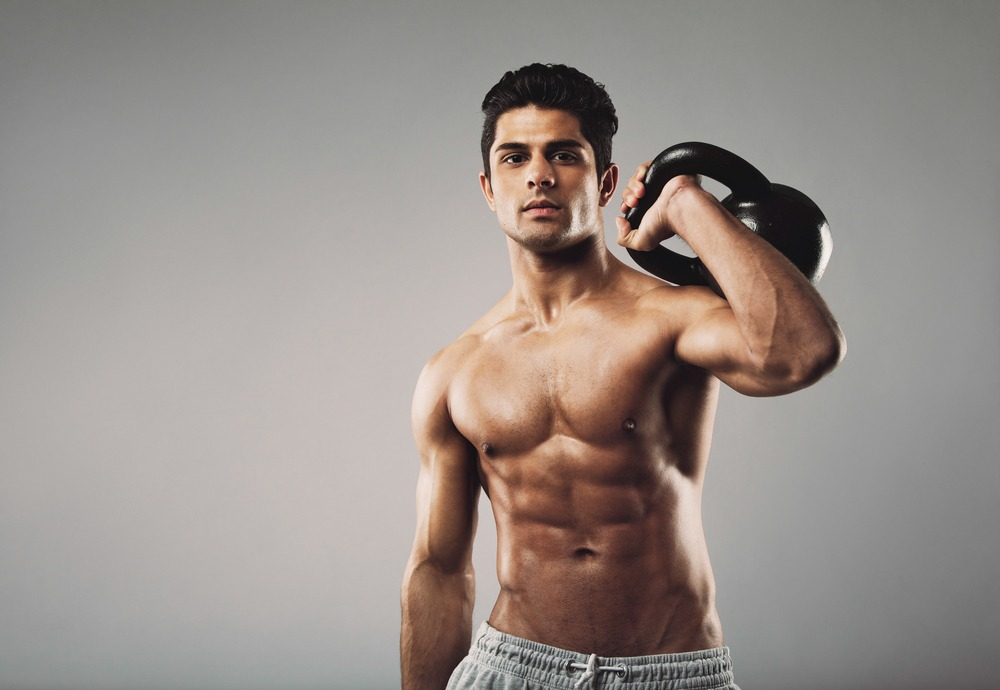 ripped guy lifting a kettle bell by his shoulder