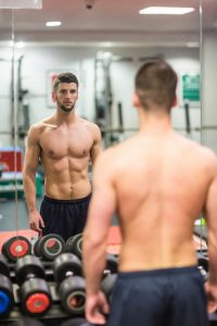fit shirtless guy looking at himself on gym mirror