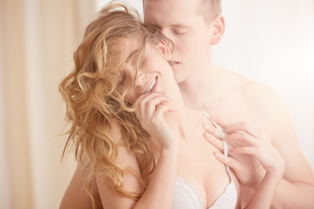 woman getting aroused by man whispering in her ears