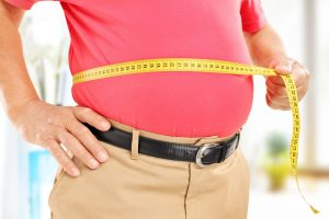 elder man measures waist for weight loss