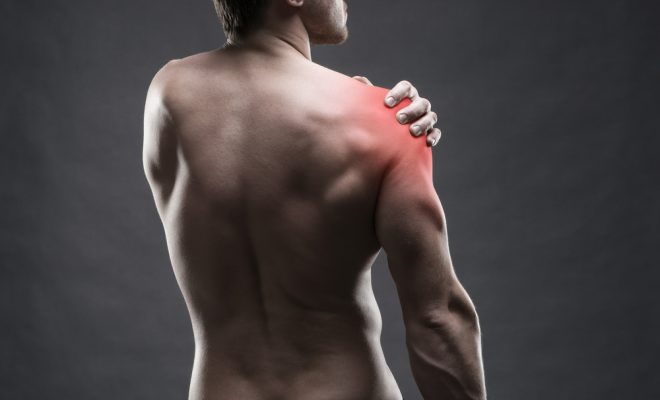 man with muscle pain holds shoulder